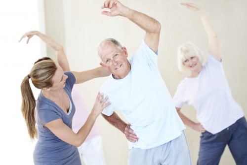 Portrait of an elderly man doing stretches and being assisted by a young instructor